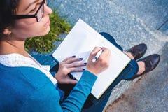 Estudante novo com caderno Em linha estudando fora o conceito Fotos de Stock