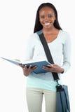 Estudante novo de sorriso com leitura do saco em seu livro fotos de stock