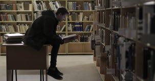 Estudante novo do retrato que lê um livro na biblioteca video estoque