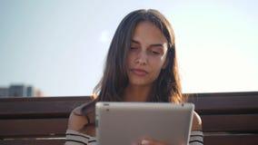 Estudante novo feliz com uma tabuleta que senta-se no banco e que lê em um parque do verão Mulher bonita moreno da menina vídeos de arquivo