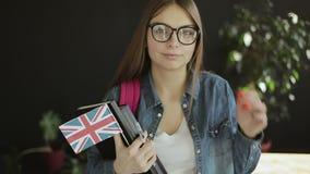 Estudante novo Holding British Flag e livros video estoque