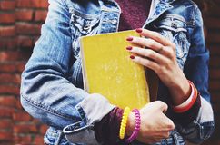 Estudante novo no revestimento das calças de brim que guarda livros em suas mãos Fotografia de Stock