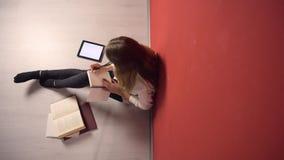 Estudante novo persistente Girl Studying no assoalho filme