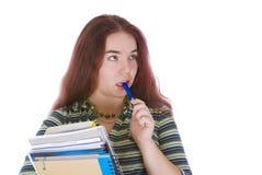 Estudante novo que está com uma pilha de livros imagem de stock