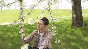 Estudante novo que estuda o assunto com um jardim do portátil na primavera filme
