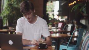 Estudante novo que faz trabalhos de casa no café, freelancer que usa o lápis para tirar no papel, lugar de trabalho moderno que s video estoque