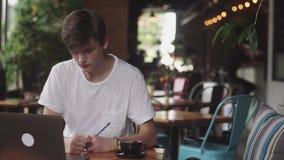 Estudante novo que faz trabalhos de casa no café, freelancer que usa o lápis para tirar no papel, lugar de trabalho moderno que s vídeos de arquivo