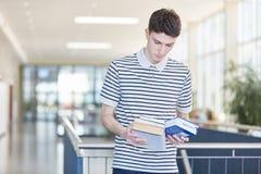 Estudante novo que guarda livros de texto foto de stock