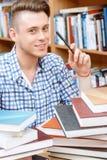 Estudante novo que trabalha em uma biblioteca Foto de Stock