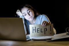 Estudante novo que trabalha tarde na noite em seu computador que guarda um sinal da ajuda foto de stock royalty free