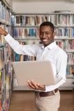 Estudante novo Using His Laptop em uma biblioteca foto de stock royalty free