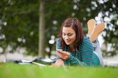 Estudante ocasional atrativo que encontra-se em texting da grama imagens de stock royalty free