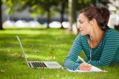 Estudante ocasional atrativo que encontra-se na grama que toma notas imagens de stock royalty free