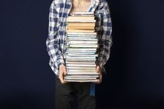 Estudante ocasional para levar a pilha enorme de livros no fundo escuro f foto de stock royalty free