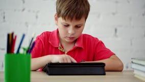 A estudante olha a tabuleta vídeos de arquivo