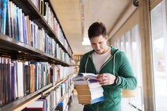 Estudante ou homem feliz com o livro na biblioteca fotos de stock