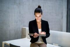 Estudante ou mulher de negócios nova que sentam-se na mesa na sala em uma biblioteca ou em um escritório, usando a tabuleta imagem de stock royalty free