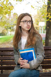 Estudante pensativo com os vidros que sentam-se no banco Fotografia de Stock Royalty Free