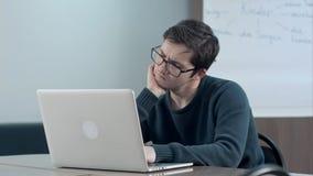 Estudante pensativo com portátil que estuda na biblioteca da universidade Fotografia de Stock Royalty Free
