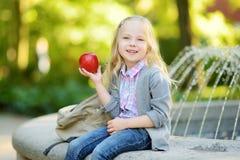 Estudante pequena adorável que estuda fora no dia brilhante do outono Estudante novo que faz seus trabalhos de casa Educação para Imagens de Stock