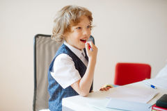 Estudante pequena bonito que senta-se em uma mesa da escola com sonho de vistas foto de stock royalty free