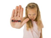 Estudante pequena doce e assustado que mostra tiranizar da palavra riscado escrito em sua mão Foto de Stock Royalty Free