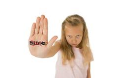 Estudante pequena doce e assustado que mostra tiranizar da palavra riscado escrito em sua mão Fotografia de Stock Royalty Free