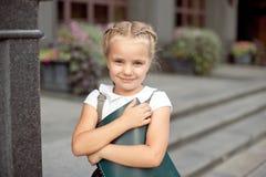 Estudante pequena feliz com o livro que vai para tr?s ? escola exterior imagens de stock royalty free