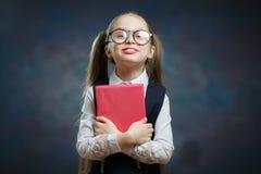 Estudante pequena feliz no livro uniforme da posse firmemente fotografia de stock
