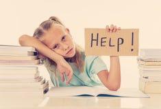 Estudante pequena frustrante que sente uma falha incapaz de concentrar-se na leitura e que escreve o problema de aprendizagem das fotos de stock