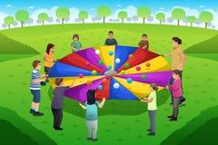 Estudante Playing Rainbow Parachute do professor Fotografia de Stock Royalty Free