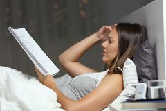 Estudante preocupado que estuda horas atrasadas na cama em casa imagens de stock royalty free