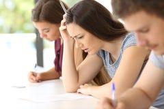 Estudante preocupado que tenta fazer um exame difícil fotografia de stock