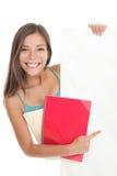 Estudante que aponta mostrando o sinal em branco do quadro de avisos Imagem de Stock
