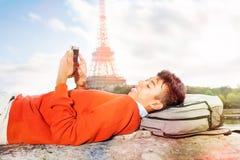 Estudante que descansa após a faculdade, usando o telefone esperto fotografia de stock royalty free