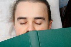 Estudante que dorme com livro Fotos de Stock Royalty Free