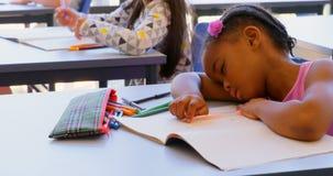 Estudante que dorme no livro na mesa na sala de aula 4k filme