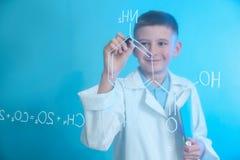 Estudante que escreve a fórmula da química na placa de vidro contra o fundo da cor fotos de stock royalty free