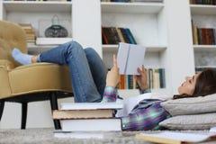 Estudante que estuda em casa, encontrando-se no assoalho contra o interior doméstico acolhedor, cercado com a pilha dos livros foto de stock royalty free