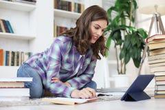 Estudante que estuda em casa, sentando-se no assoalho usando a tabuleta contra o interior doméstico acolhedor, cercado com a pilh fotografia de stock