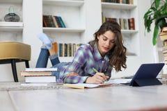 Estudante que estuda em casa, sentando-se no assoalho usando a tabuleta contra o interior doméstico acolhedor, cercado com a pilh fotografia de stock royalty free