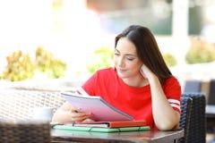 Estudante que estuda notas da leitura em um terra?o da barra fotografia de stock