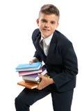 Estudante que guarda livros pesados Fotografia de Stock Royalty Free