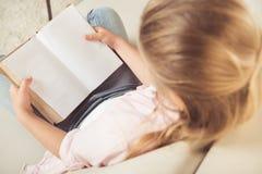 Estudante que guarda o livro vazio ao sentar-se no sofá em casa imagens de stock royalty free