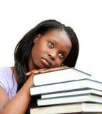Estudante que inclina-se em uma pilha de livros Imagens de Stock Royalty Free