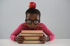 Estudante que inclina-se na pilha de livros contra o fundo branco Fotos de Stock Royalty Free