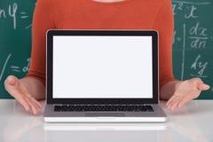 Estudante que indica o portátil com a tela vazia na sala de aula Foto de Stock