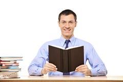 Estudante que lê um livro Fotos de Stock Royalty Free