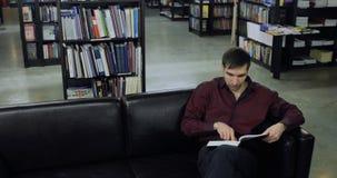 Estudante que lê um livro na biblioteca Conceito da instrução filme
