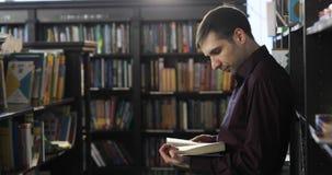 Estudante que lê um livro na biblioteca Conceito da instrução video estoque